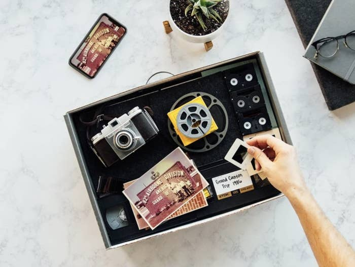 A box containing an old camera, film, postcards,