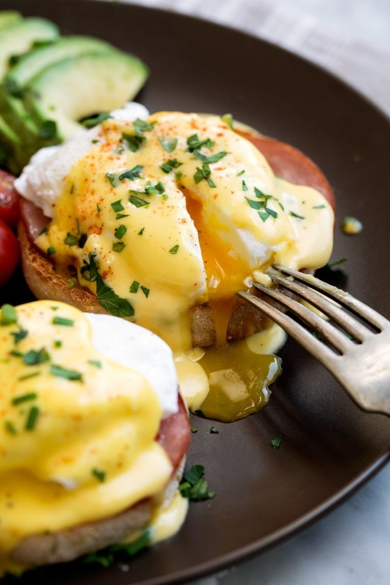Cutting into the runny interior of eggs Benedict; poached eggs on top of English muffins with Canadian bacon and hollandaise sauce.