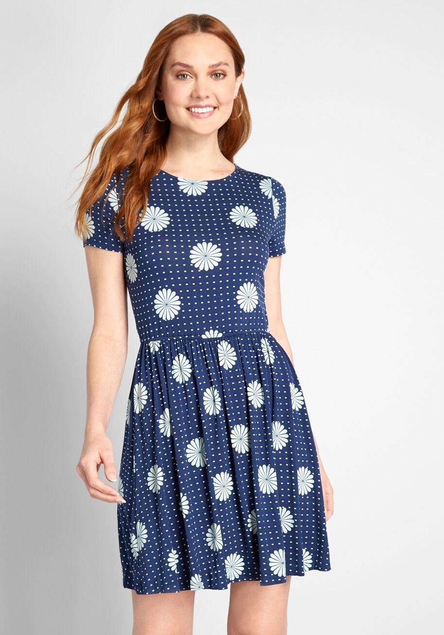 A model wearing the dress in the blue floral and polka-dot print