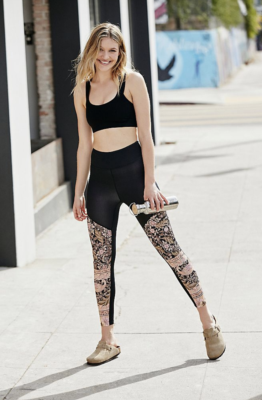 A Free People model wears the Oasis 7/8 Leggings with a floral print on the front