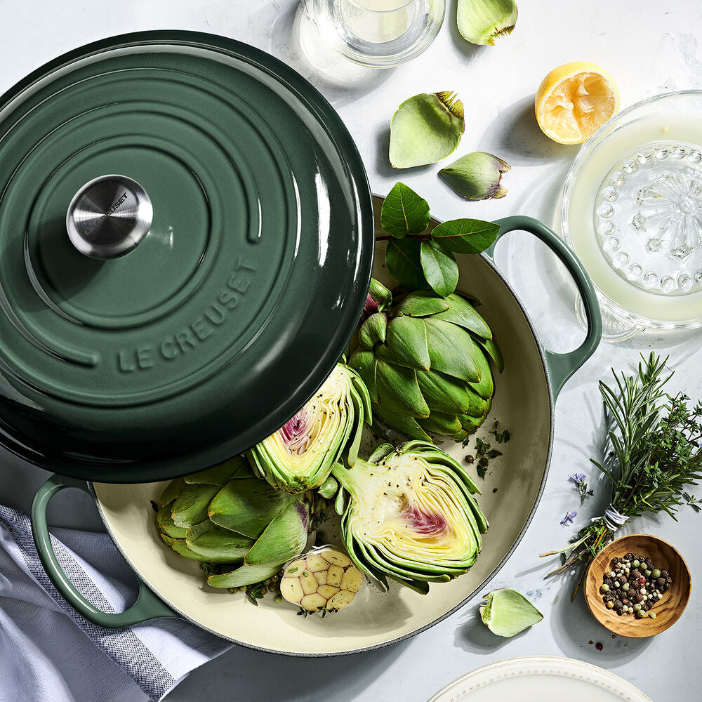 green braiser with two side handles and a lid