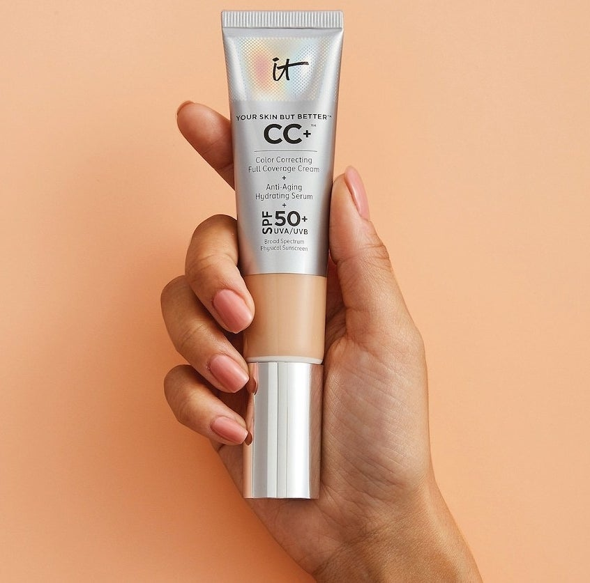 A hand holding a capped tube of the IT Cosmetics CC+ Cream with SPF 50+