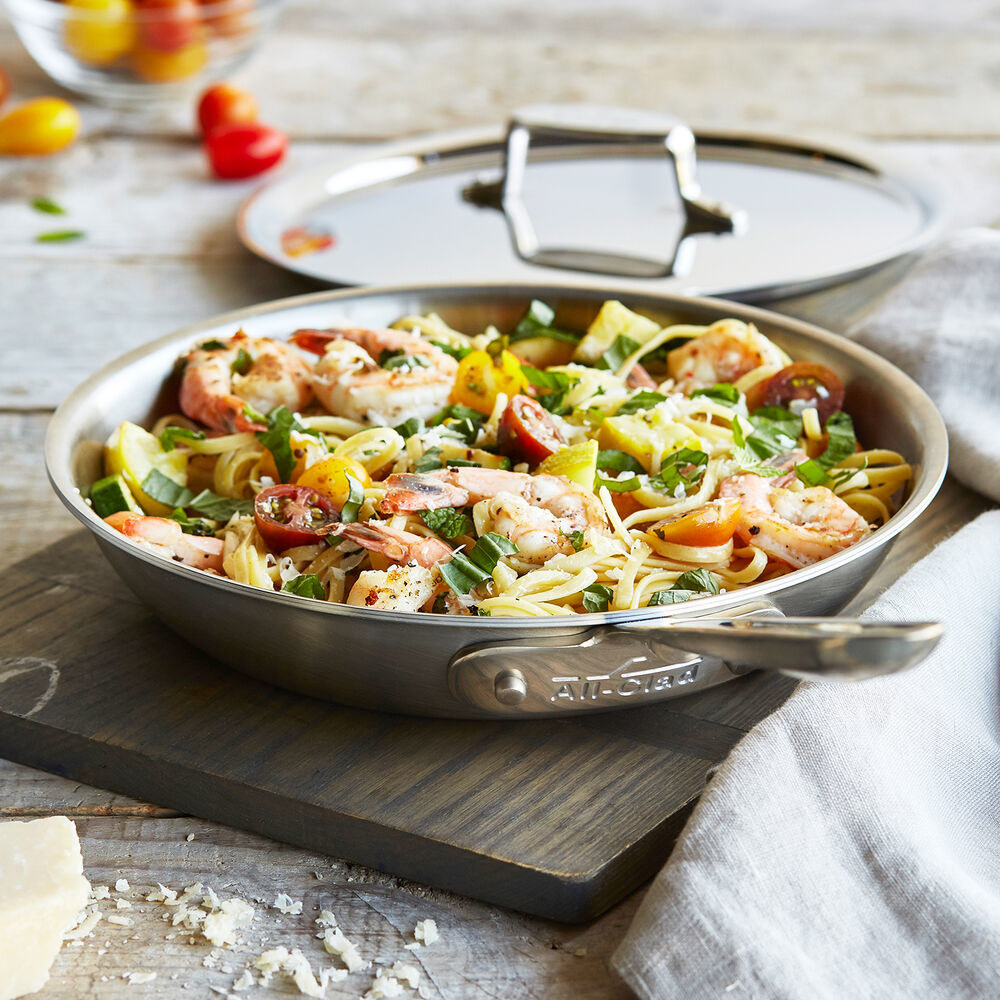 stainless steel pan full of pasta with lid on background
