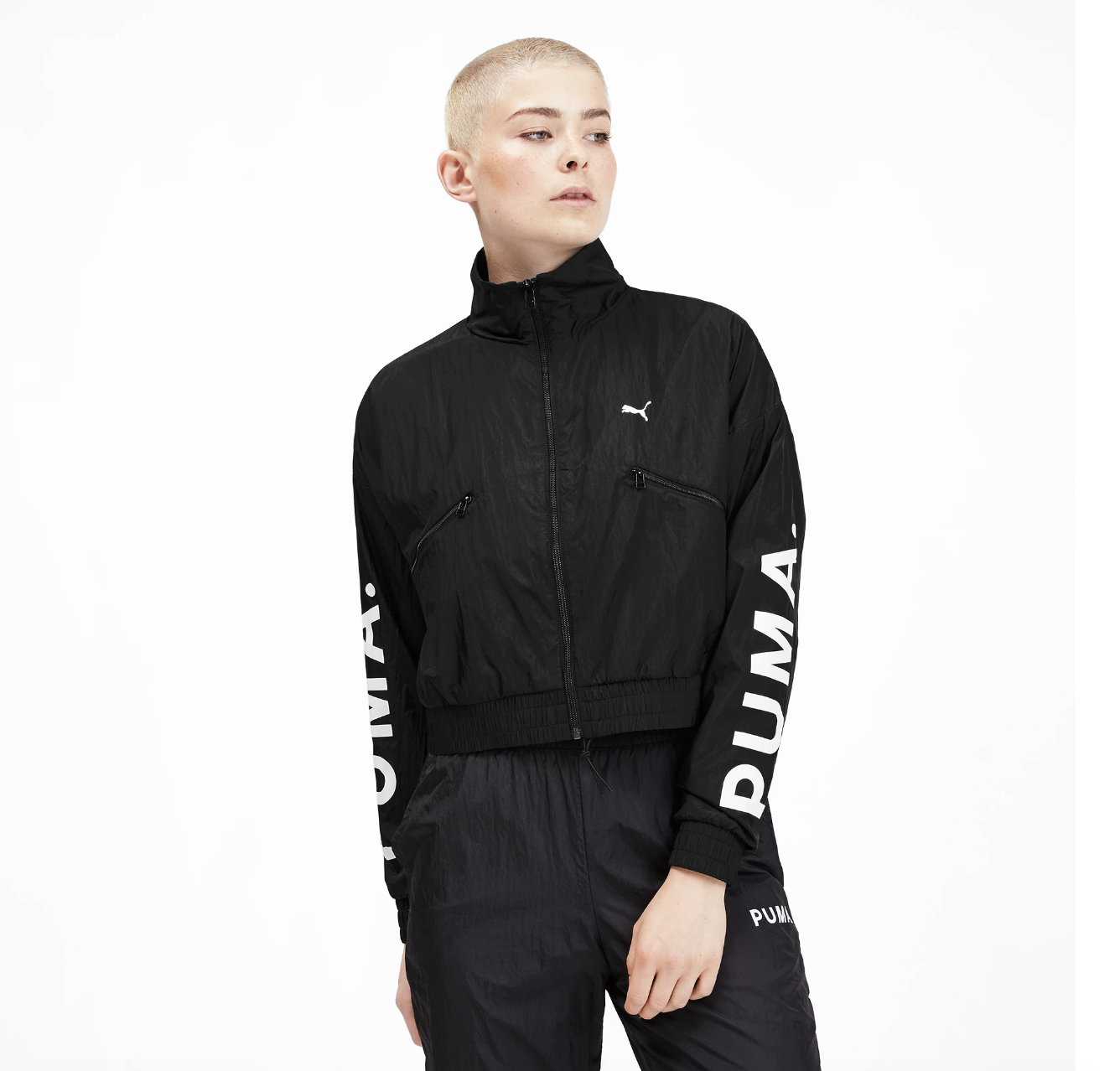 """A Puma model wears the Chase Women's Woven Jacket, which has a black color and white lettering on the side that says """"Puma"""""""