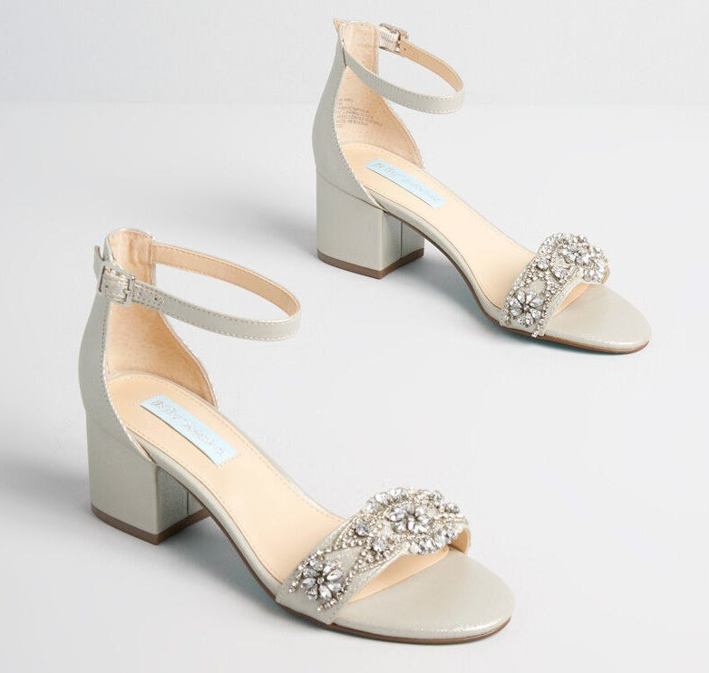 The low-heeled grey sandals with beads and rhinestones on the toe strap