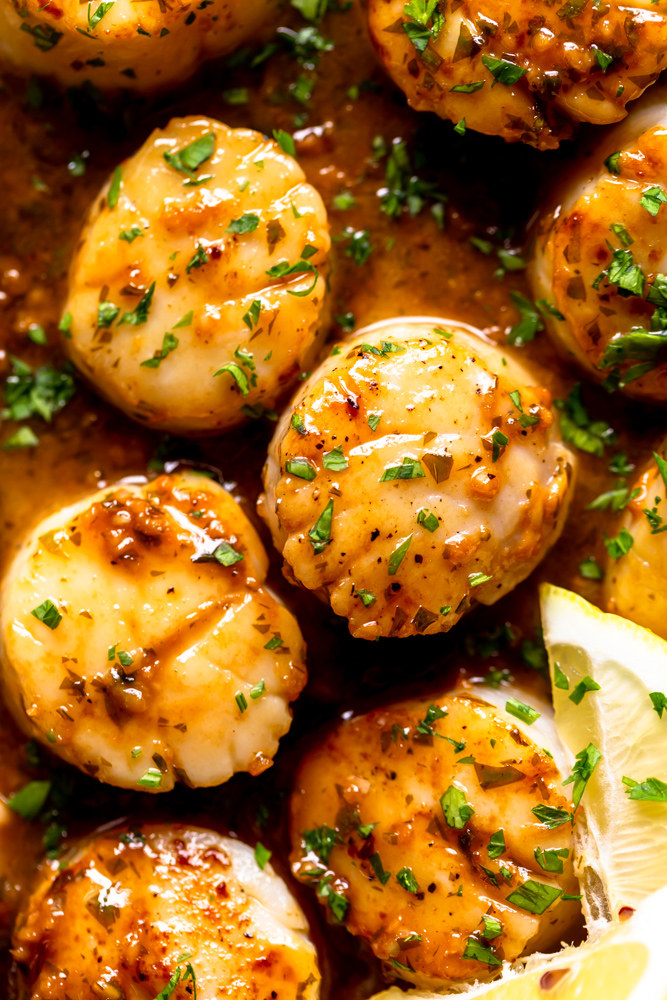 Juicy seared scallops with butter sauce and chopped parsley in a skillet.
