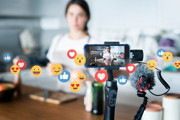 An iPhone on a stand recording a person doing a cooking demonstration. Imposed onto the image are floating Facebook reaction emojis