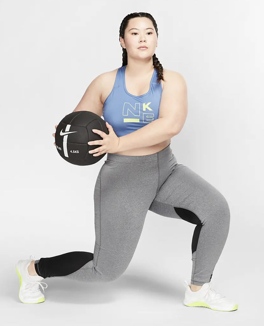 A Nike model wears a blue Swoosh Sports Bra with gray leggings while they lift a weighted ball