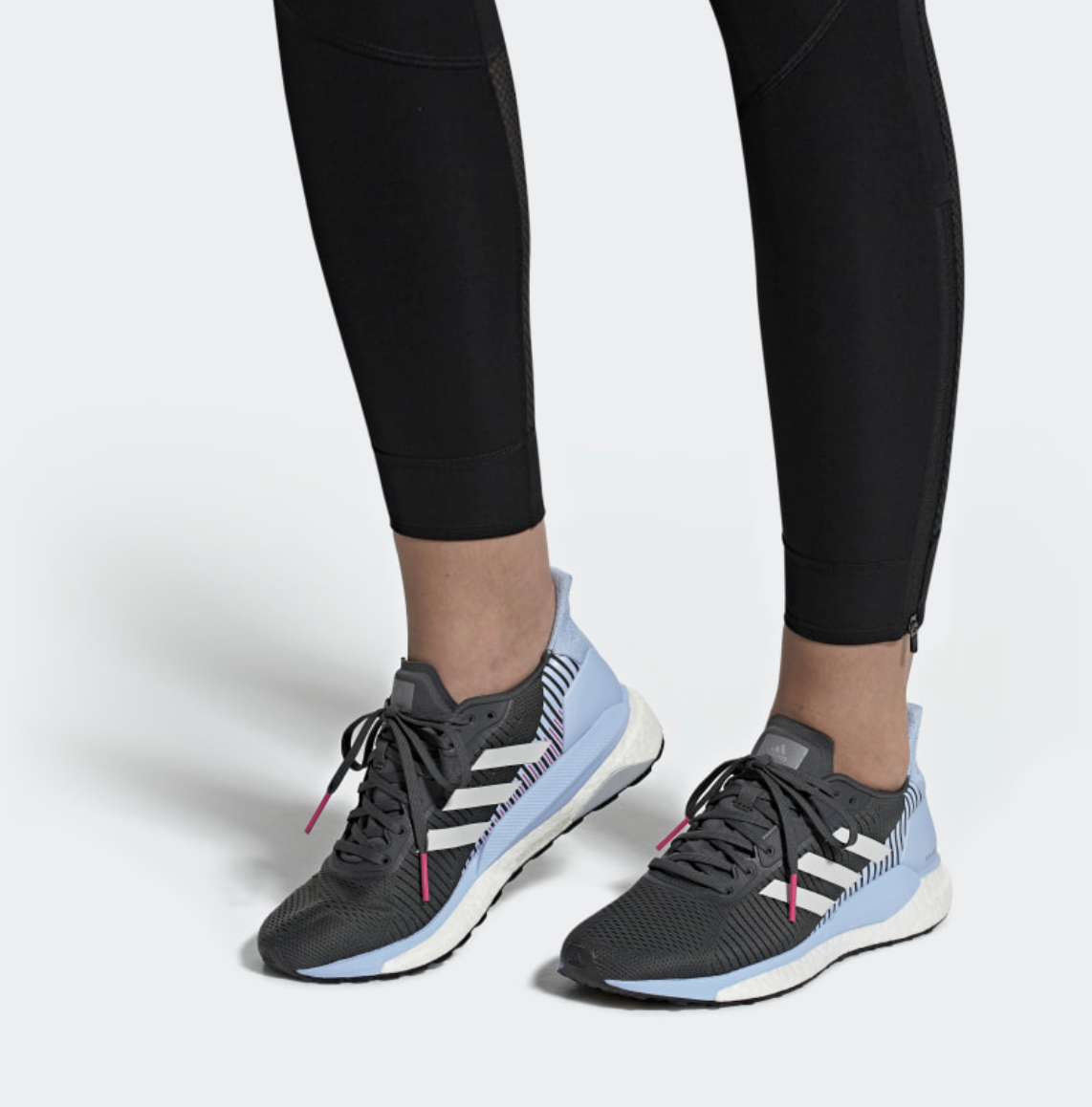 An Adidas model wears SolarGlide ST 19 Shoes that have a black toe section and a light blue heel section
