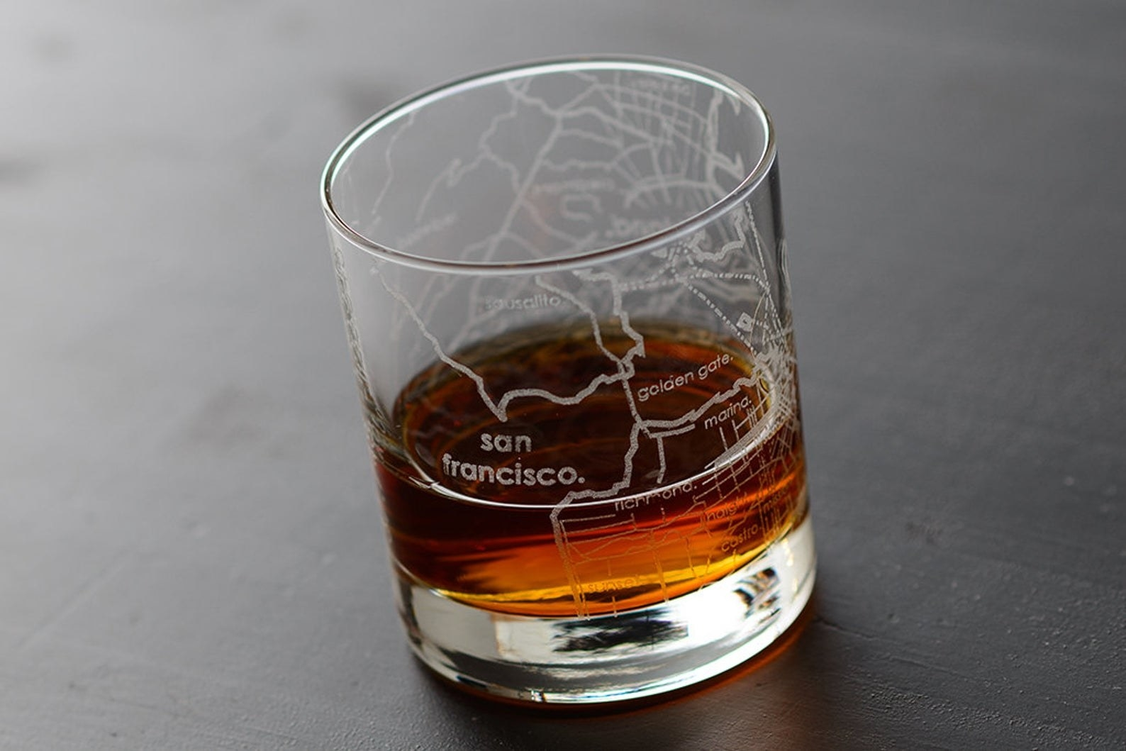 A transparent whiskey glass with an etched map of San Francisco