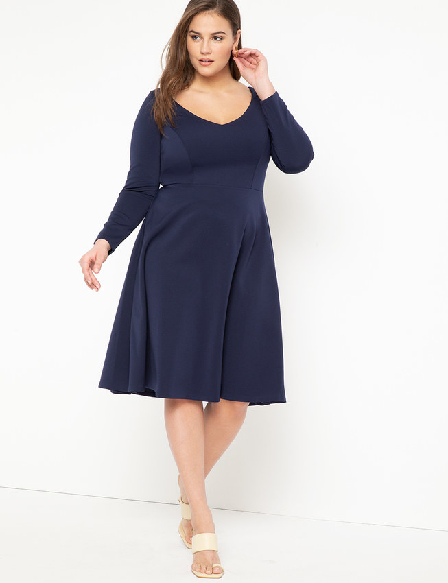 A model wearing the dress in navy blue with cream heels