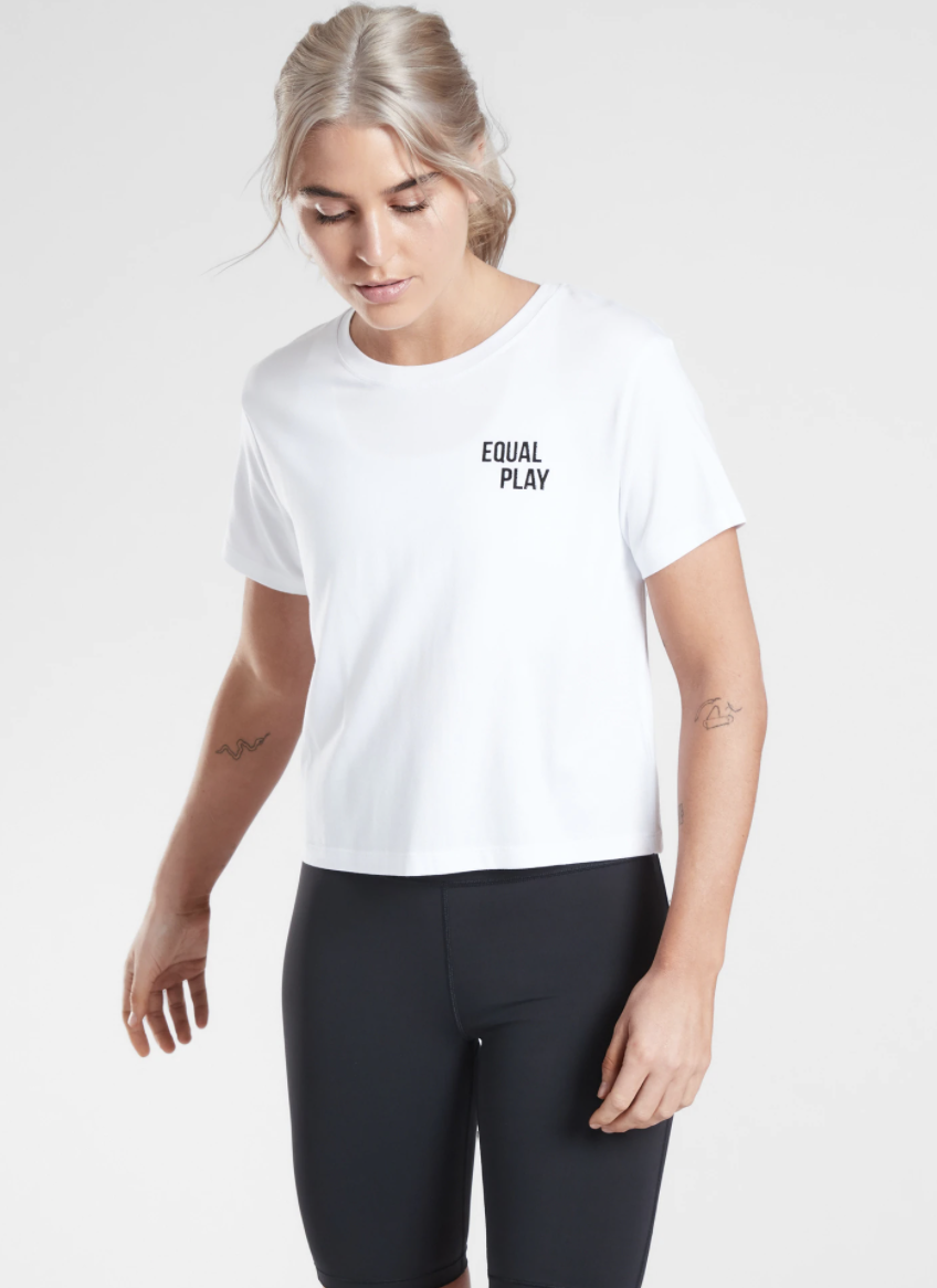 """An Athleta model wears a white T-shirt with the words """"Equal Play"""" on the front"""