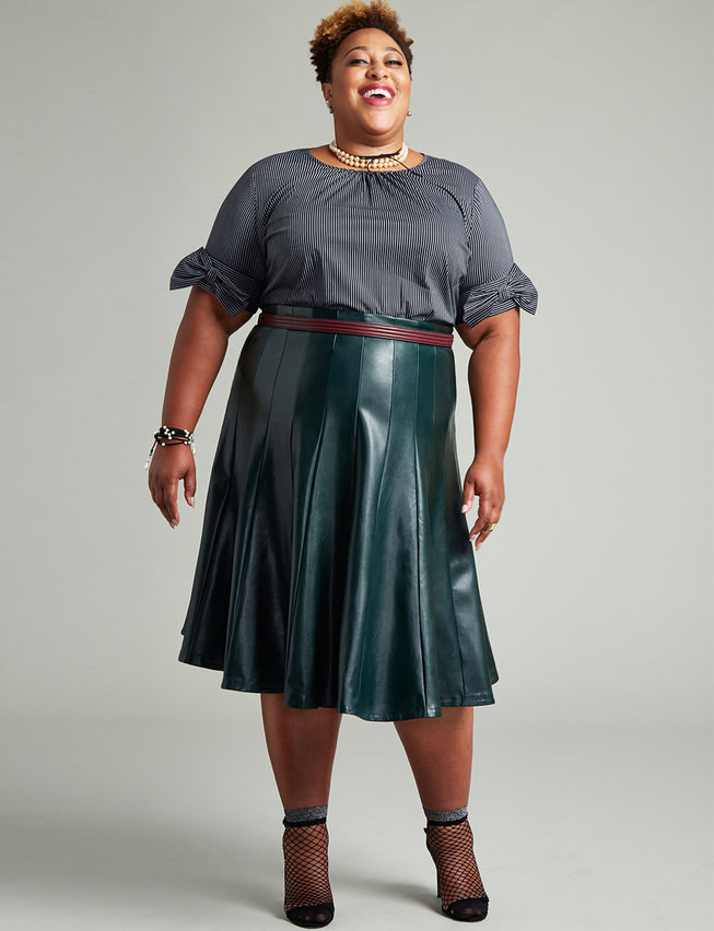 A model wearing the skirt with a belt, a blouse, a necklace, and boots