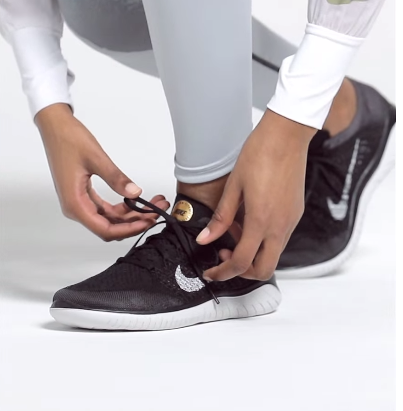 A Nike model laces up a pair of black Free RN Flyknit 2018 sneakers