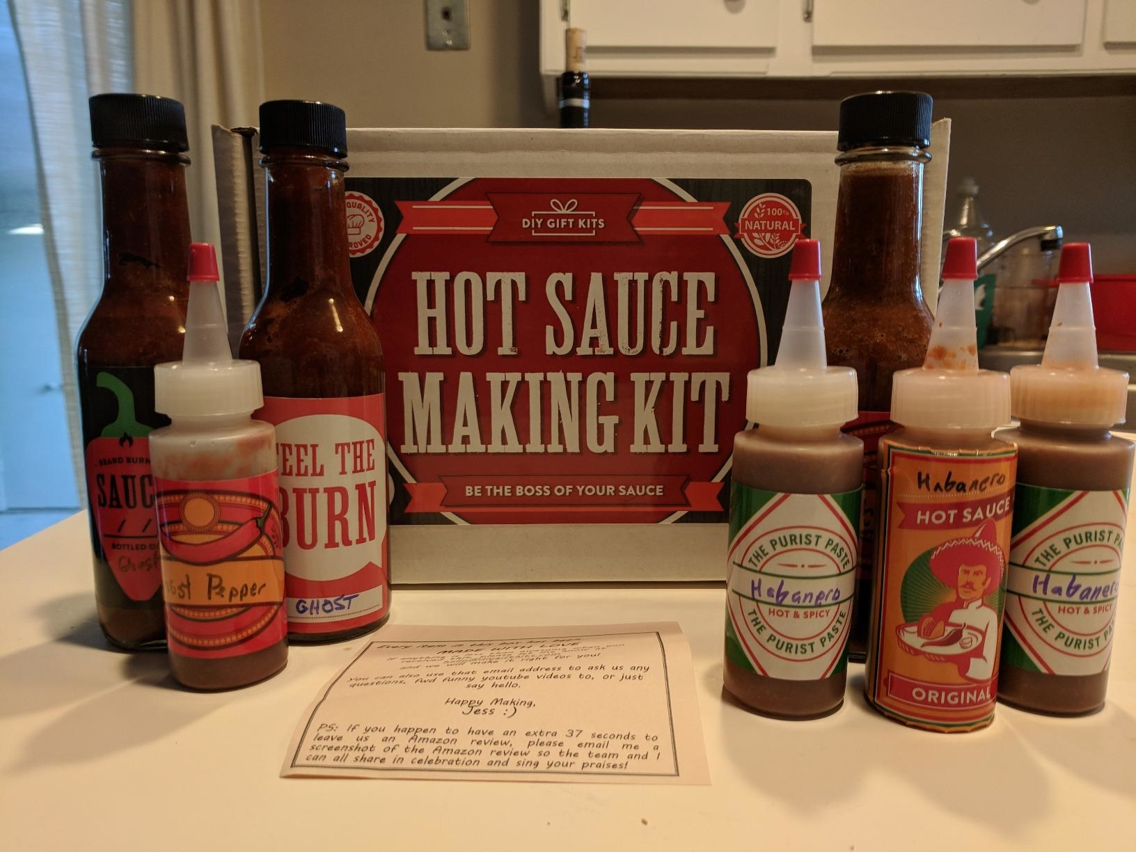 Seven kinds of homemade hot sauce bottled in front of the hot sauce making kit.