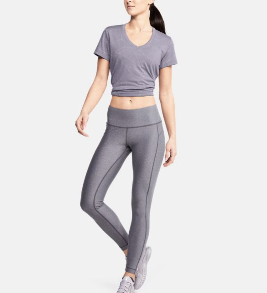 An Under Armour model wears a purple jacquard T-shirt with gray leggings
