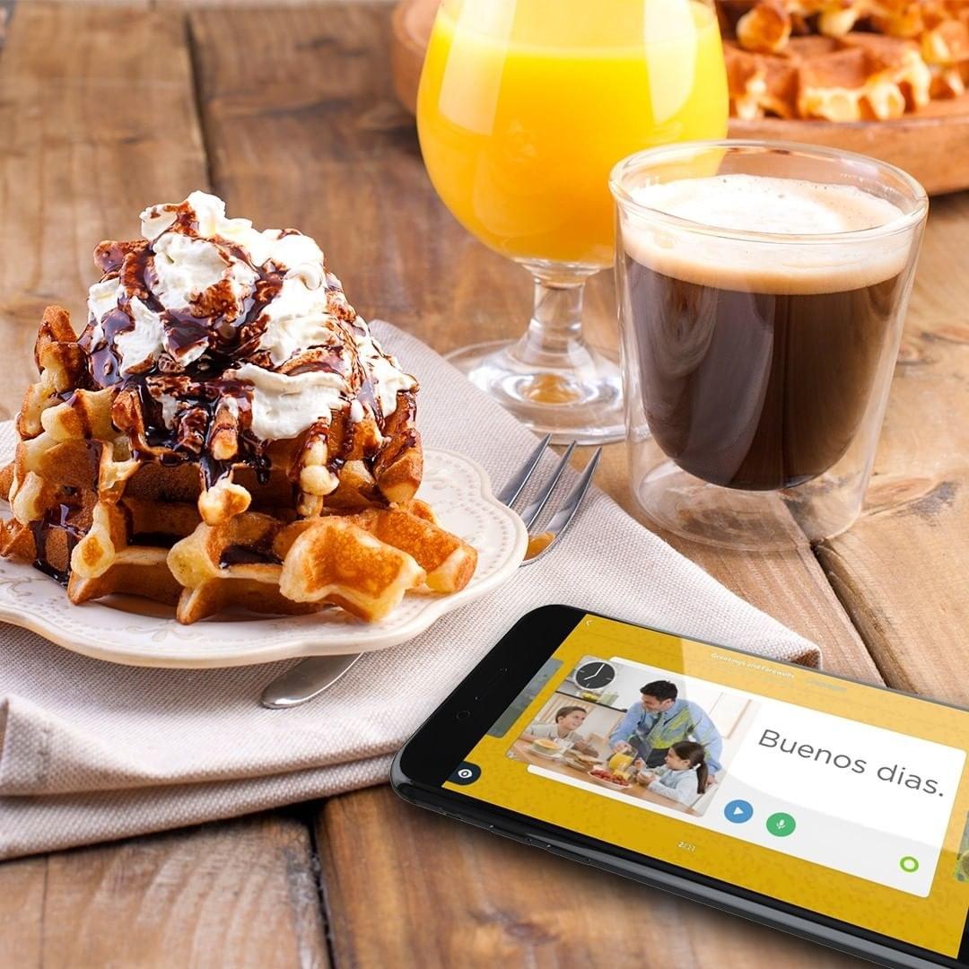 """A phone screen shows a virtual flash card that reads, """"Buenos dias"""""""