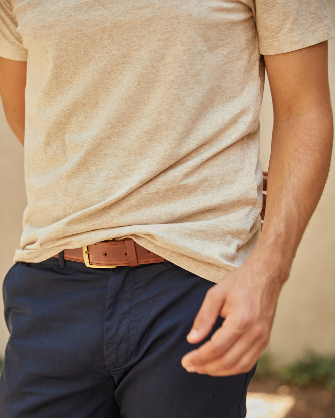 person wearing the leather belt with brass hardware with a T-shirt