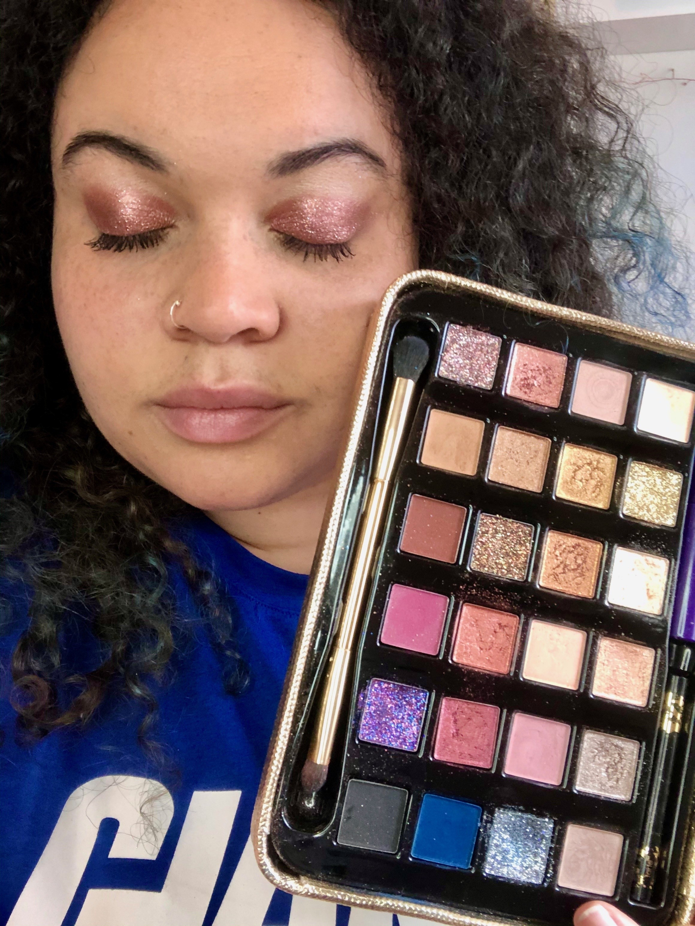 BuzzFeed Shopping reviewer holding palette and wearing pink, glittery shadow
