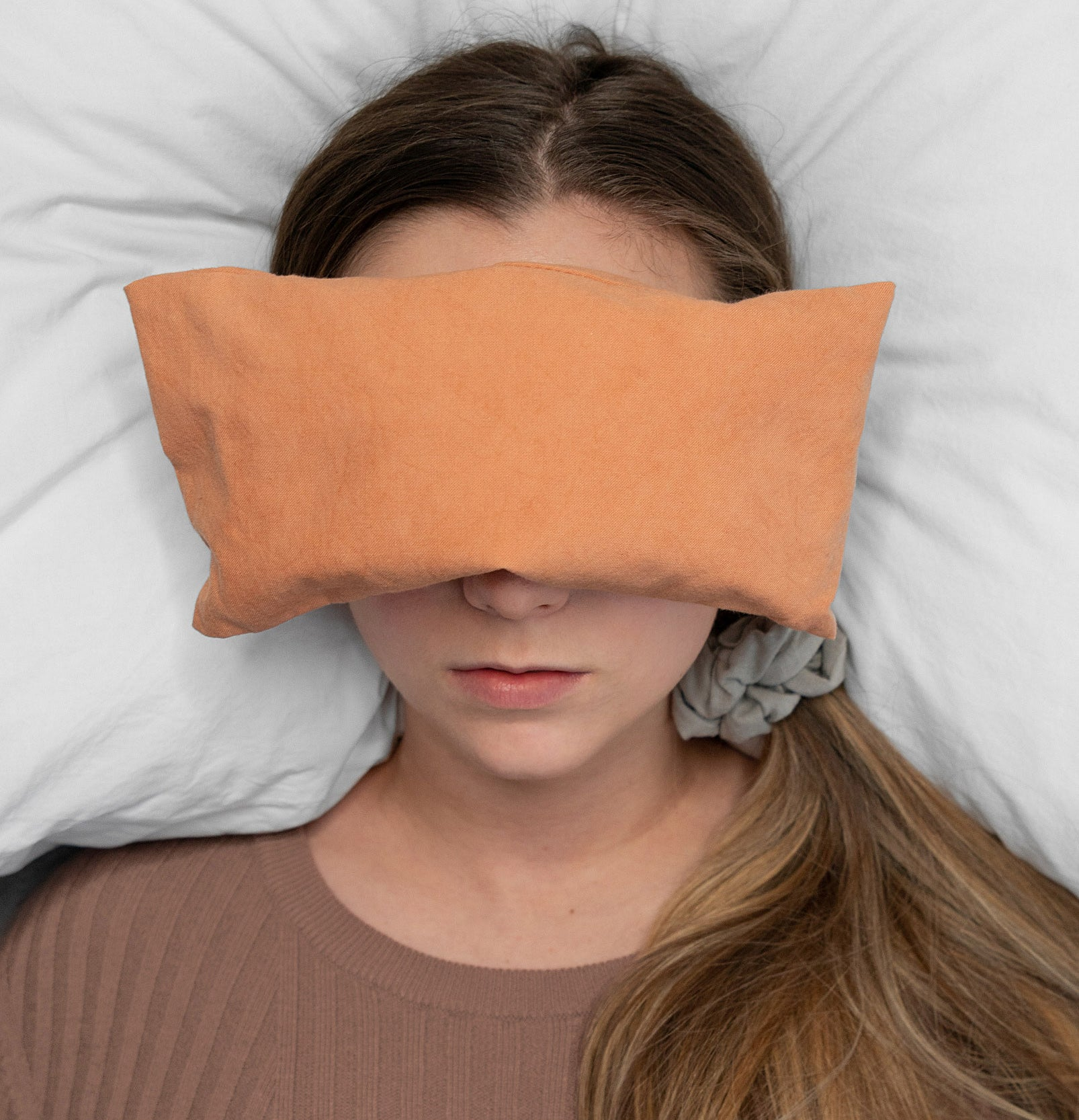 A person lying on a bed with a rectangular bean bag over their eyes