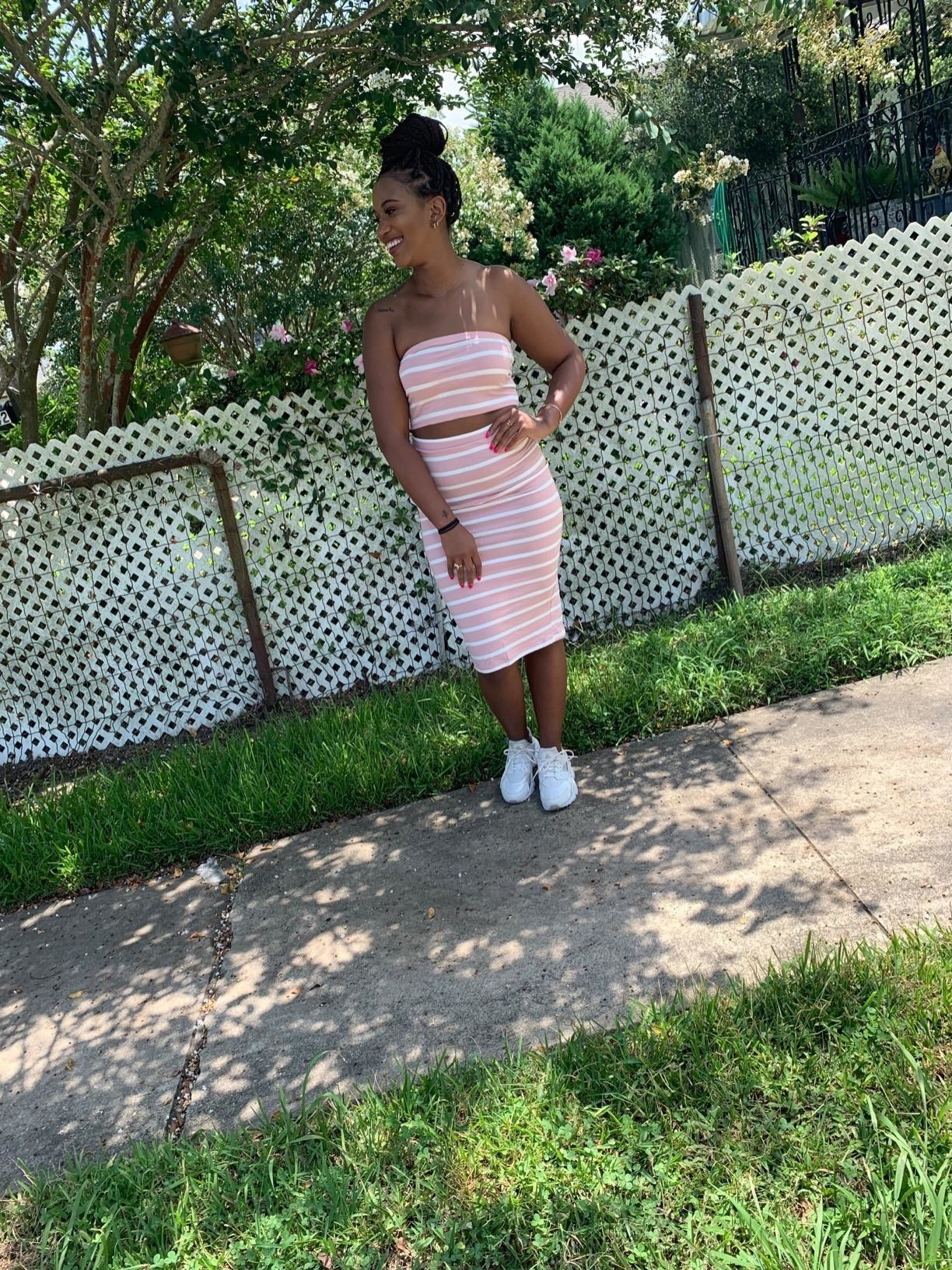 Reviewer wearing the striped set in pink, styled with sneakers