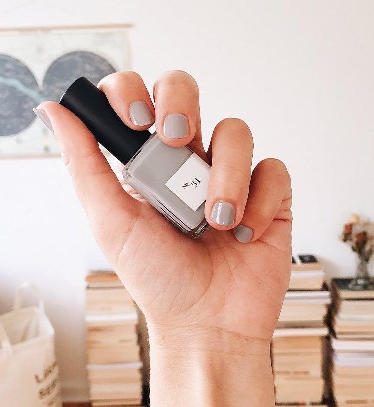 hand holding light purple nail polish bottle