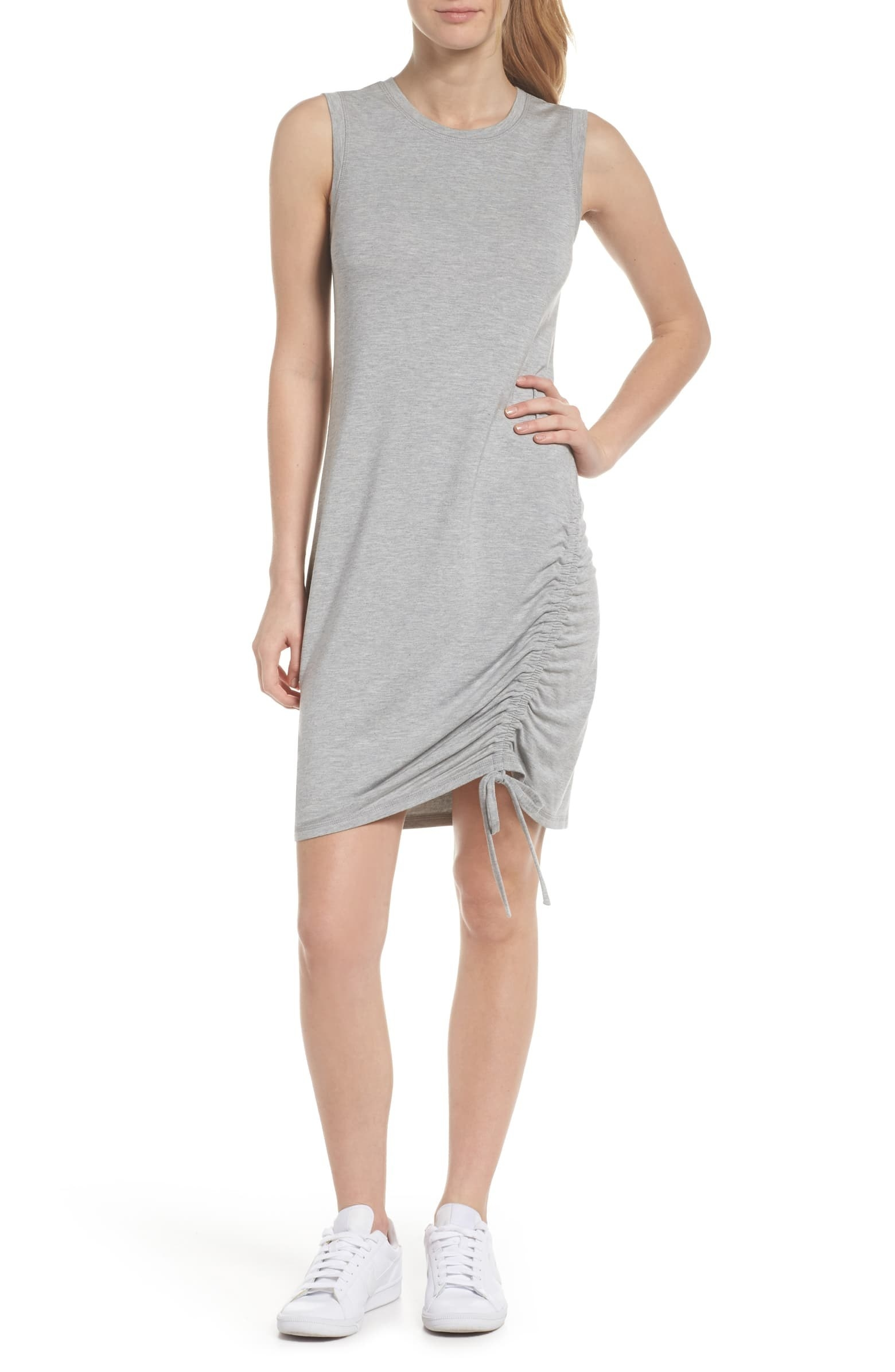 Model wearing the dress with a cinch-able ruched detailing on the side hem