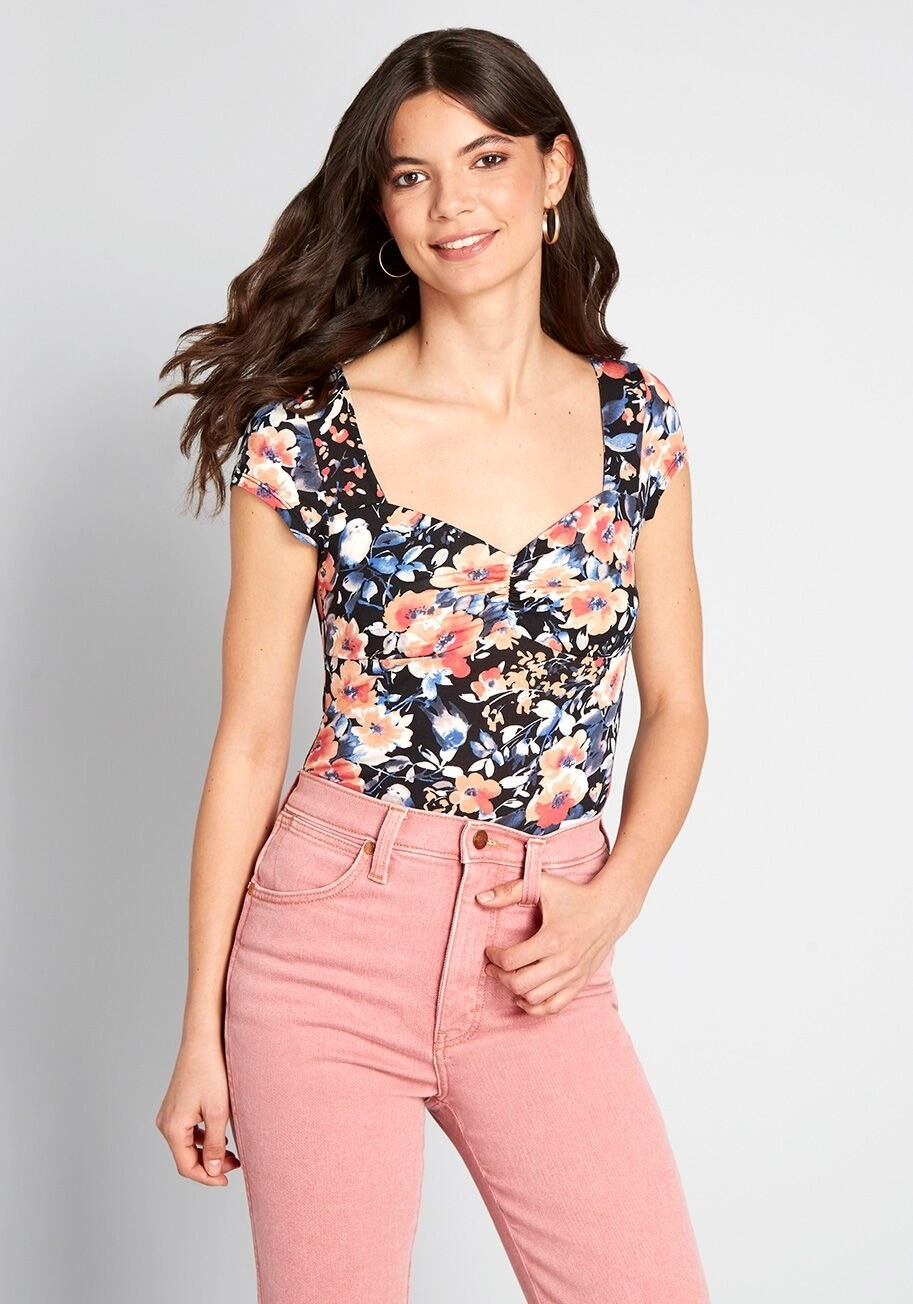 A model wearing the cap-sleeve, black, orange, and blue floral bodysuit tucked into jeans