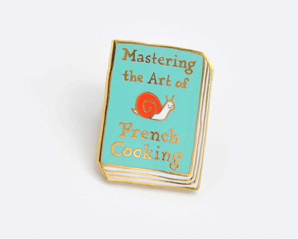 "a light blue book pin with the words ""mastering the art of french cooking"" on it in gold and a cute snail in the middle"