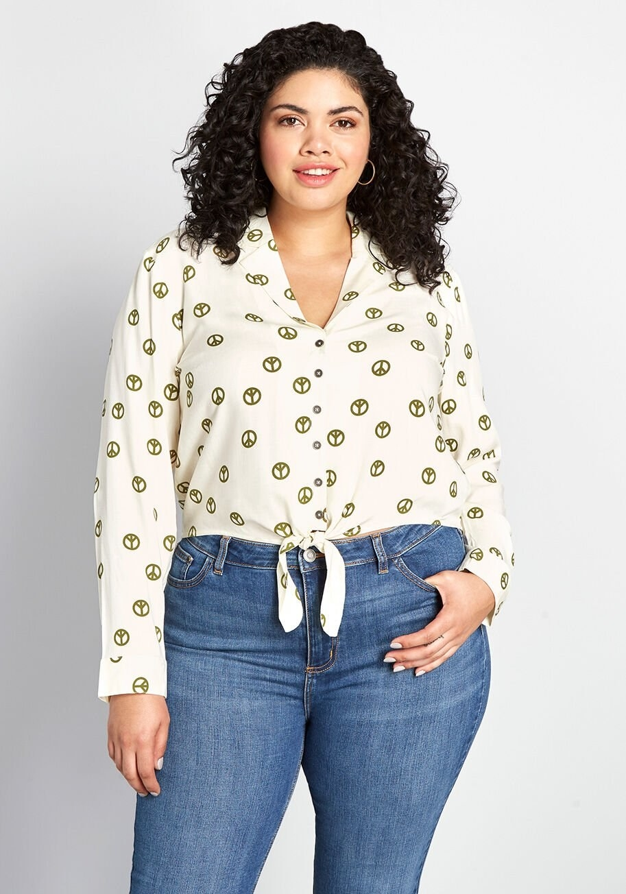 A model wearing the long-sleeved shirt, which is white and printed with green peace signs