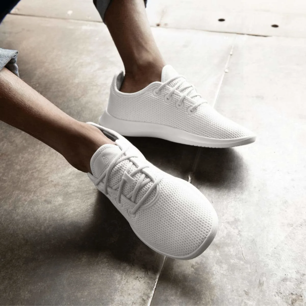 A pair of white Allbird sneaker on a model's feet