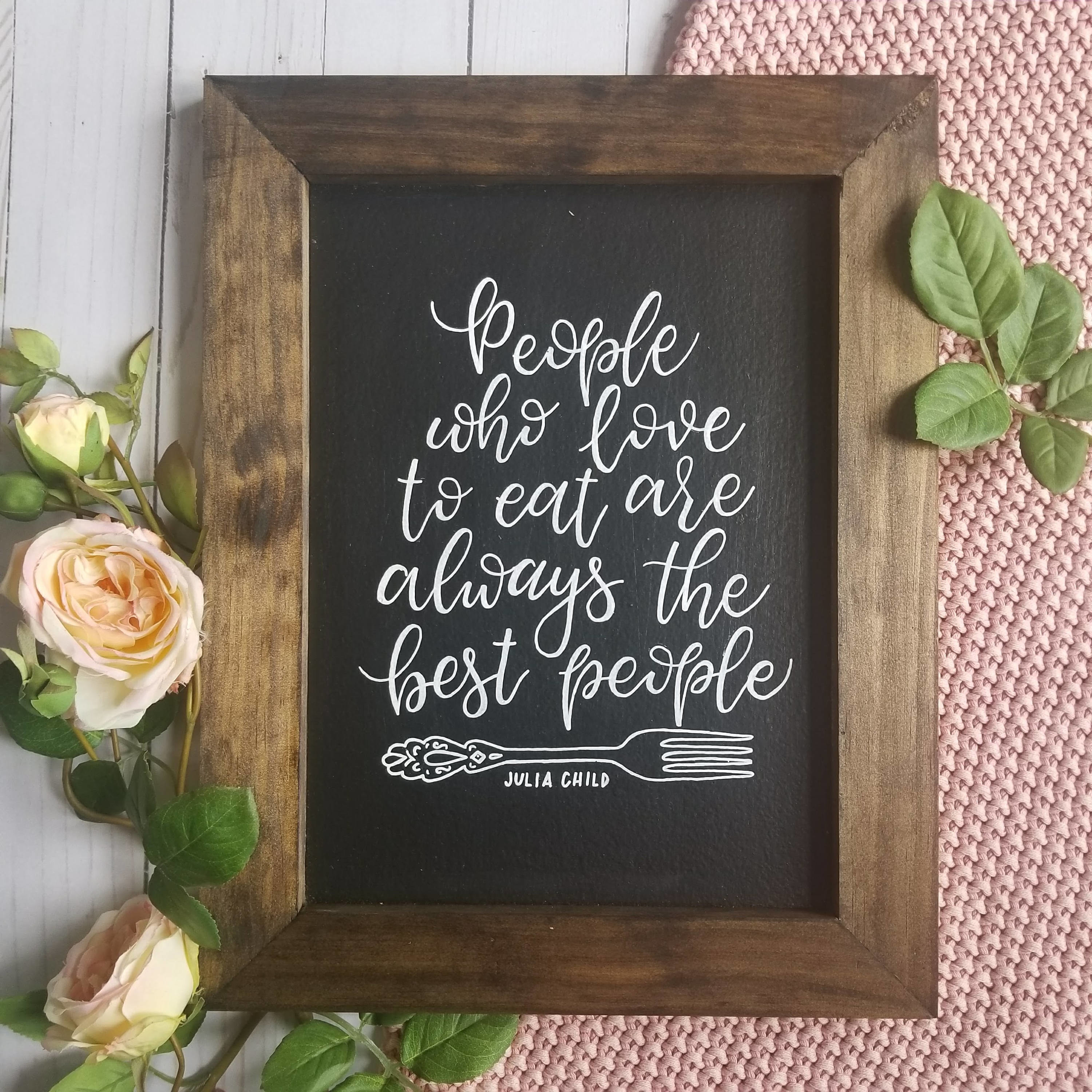 "a chalkboard-styled design with the julia child quote ""people who love to eat are always the best people"" on it and a decorative fork drawn below it"