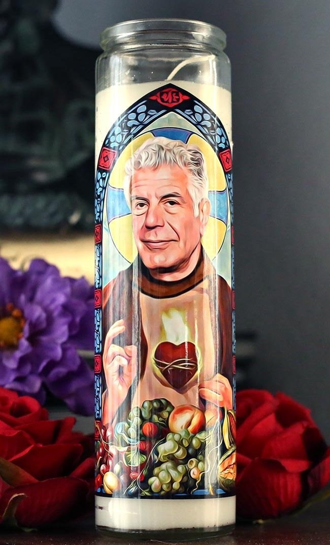 a replica of a prayer candle with an illustration of anthony bourdain on it surrounded by fruits