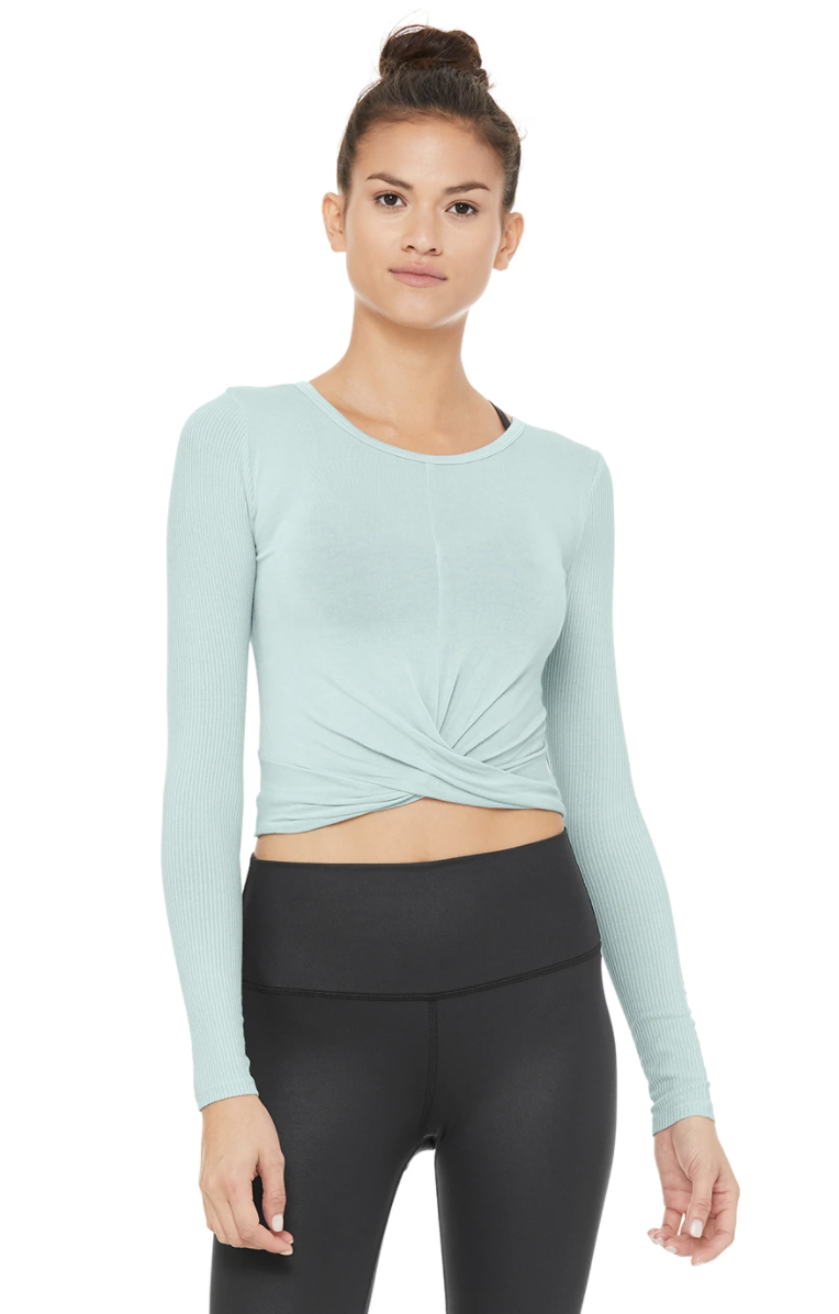 An Alo Yoga model wears a light blue Cover Long Sleeve Top with leggings