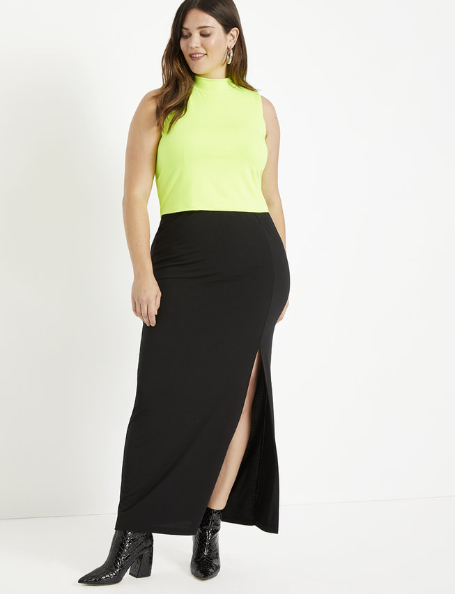 A model wearing the black slit maxi skirt with black boots and a neon tank top
