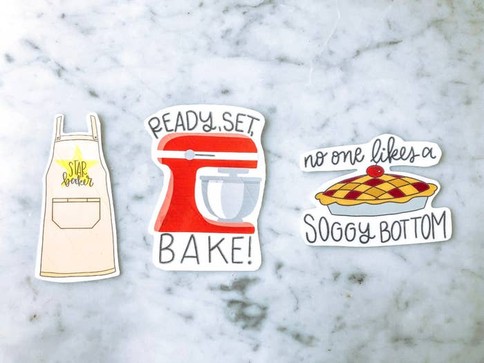 a set of three stickers: the first is an apron that says star baker, the second is a mixer that says ready set bake, the third is a pie that says no one likes a soggy bottom