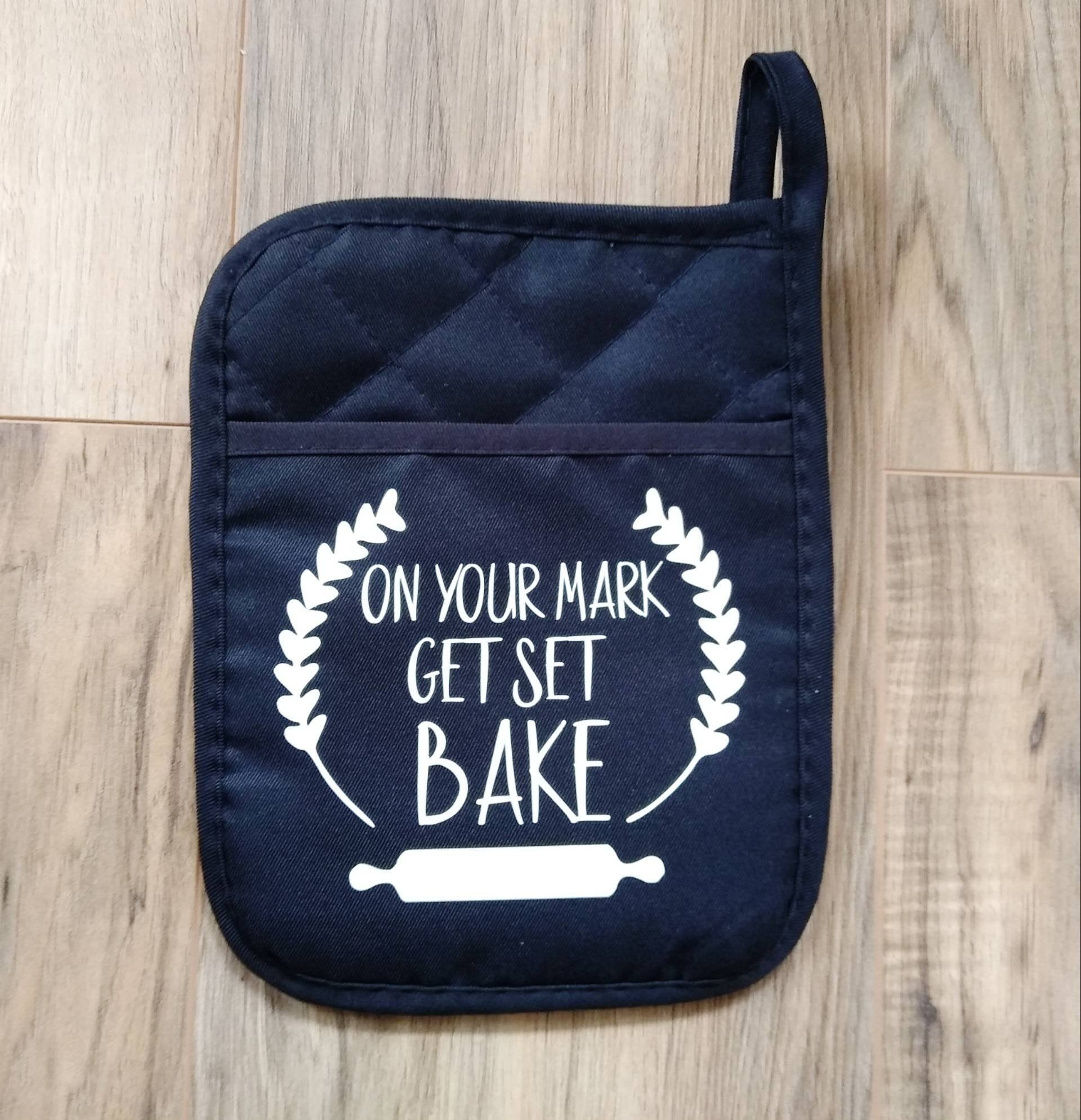 "a navy pot holder that is quilted on top and says ""on your mark get set bake"" in white between two decorative leaves and above a rolling pin"