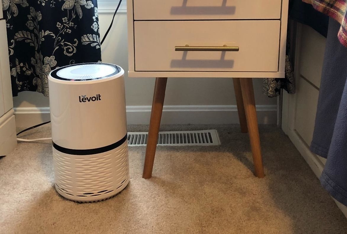 A white circular air purifier on a reviewer's bedroom floor