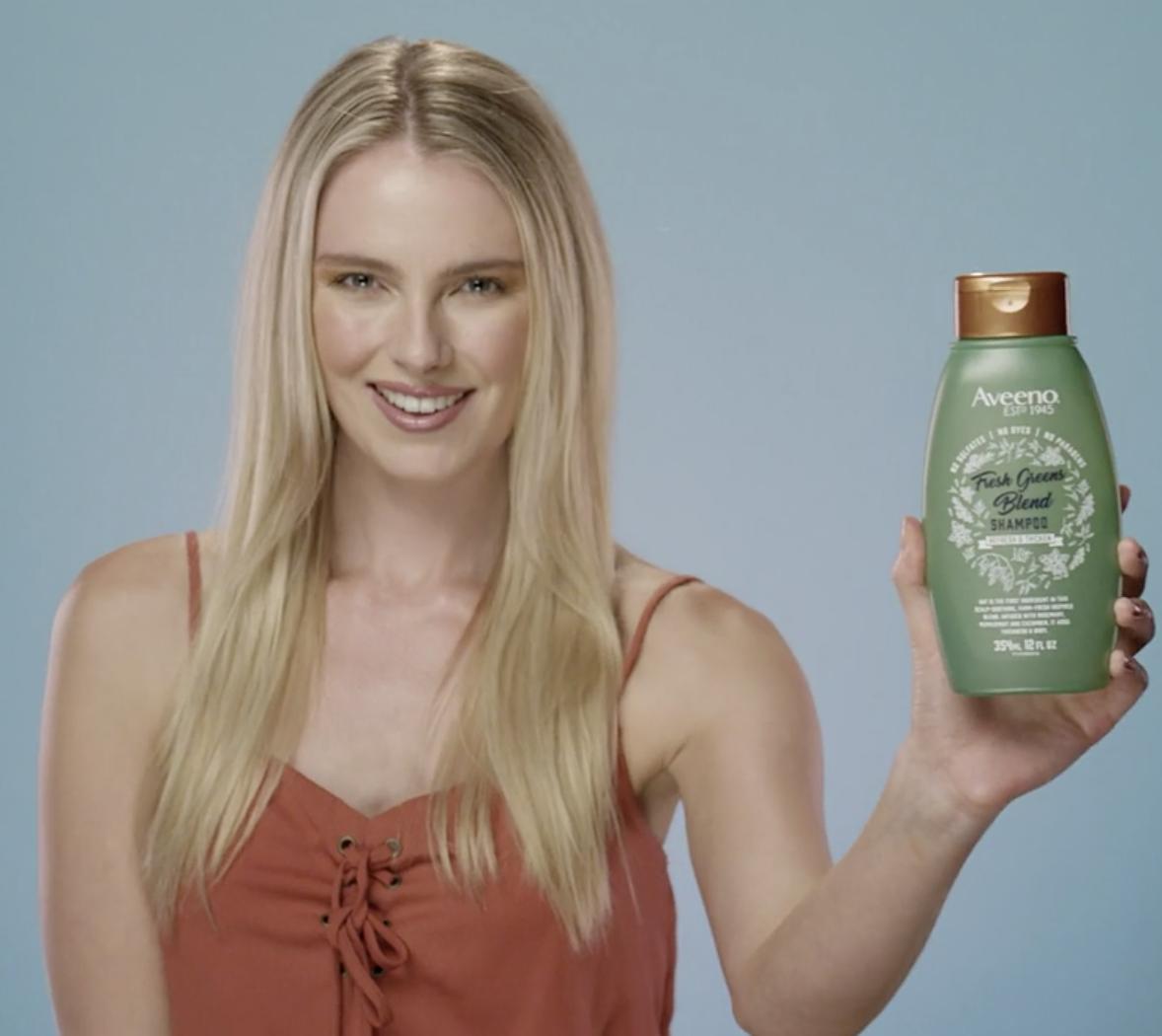 Model holding the green shampoo bottle