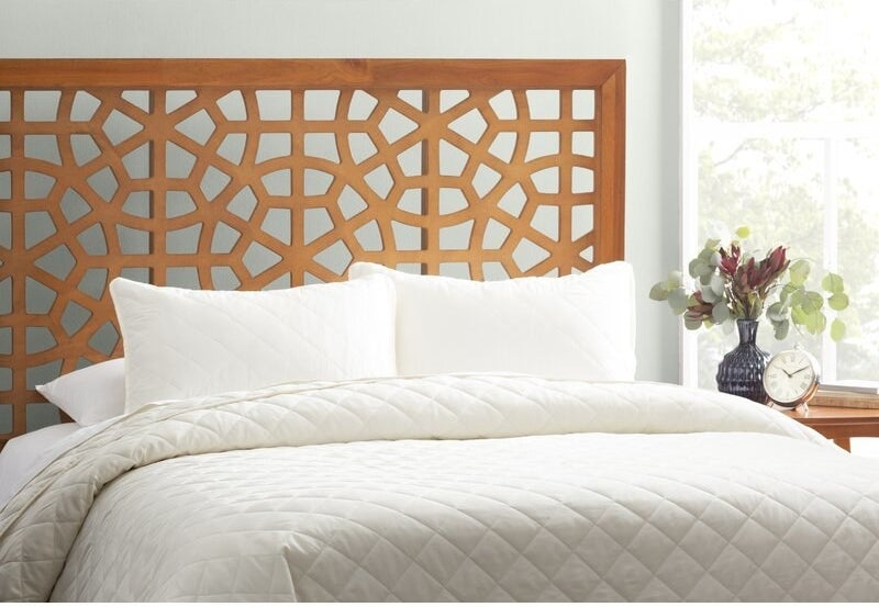 The quilt set on a bed with two pillows in matching shams