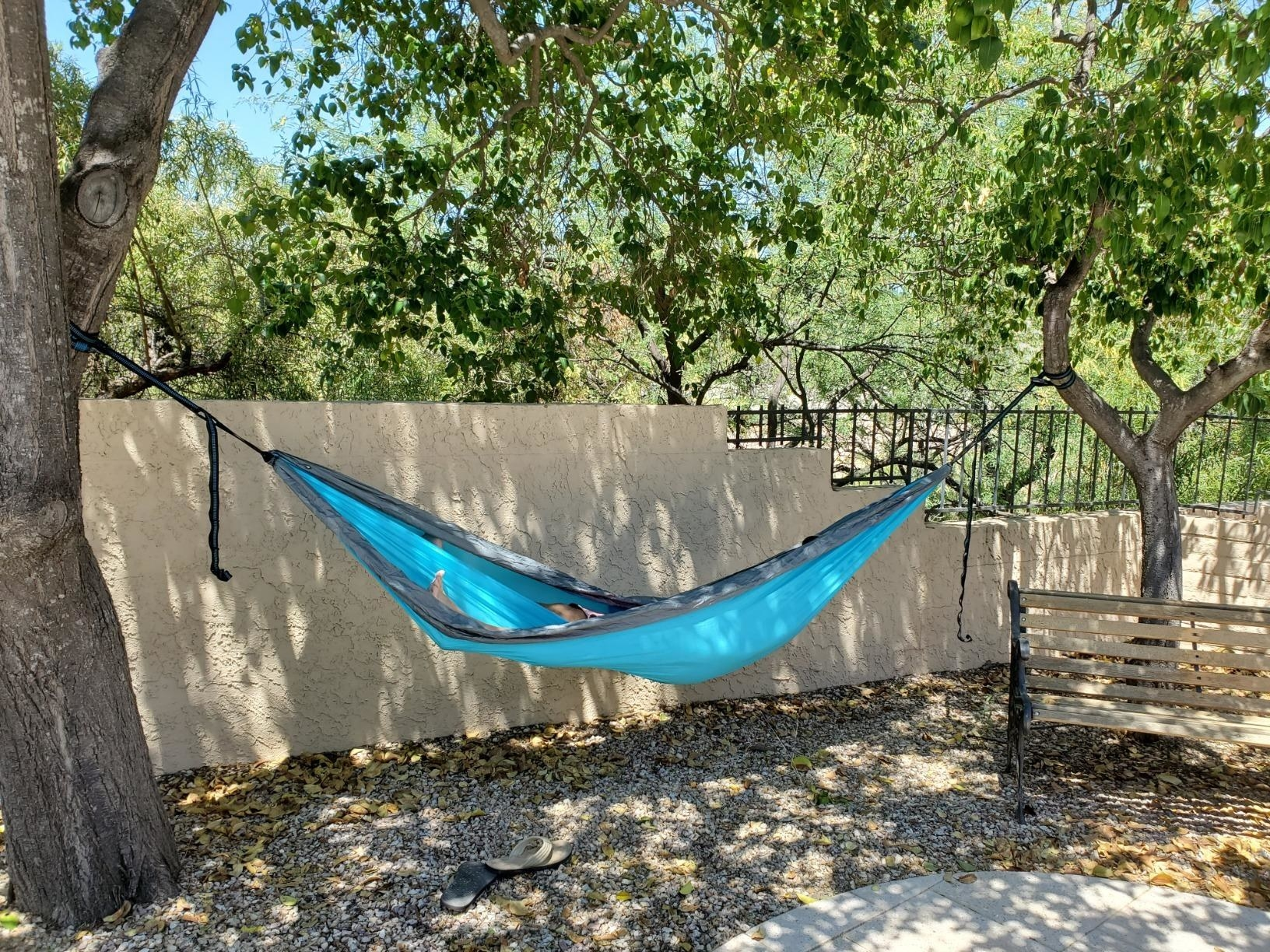 A reviewer photo of the hammock in blue tied to two trees in a yard