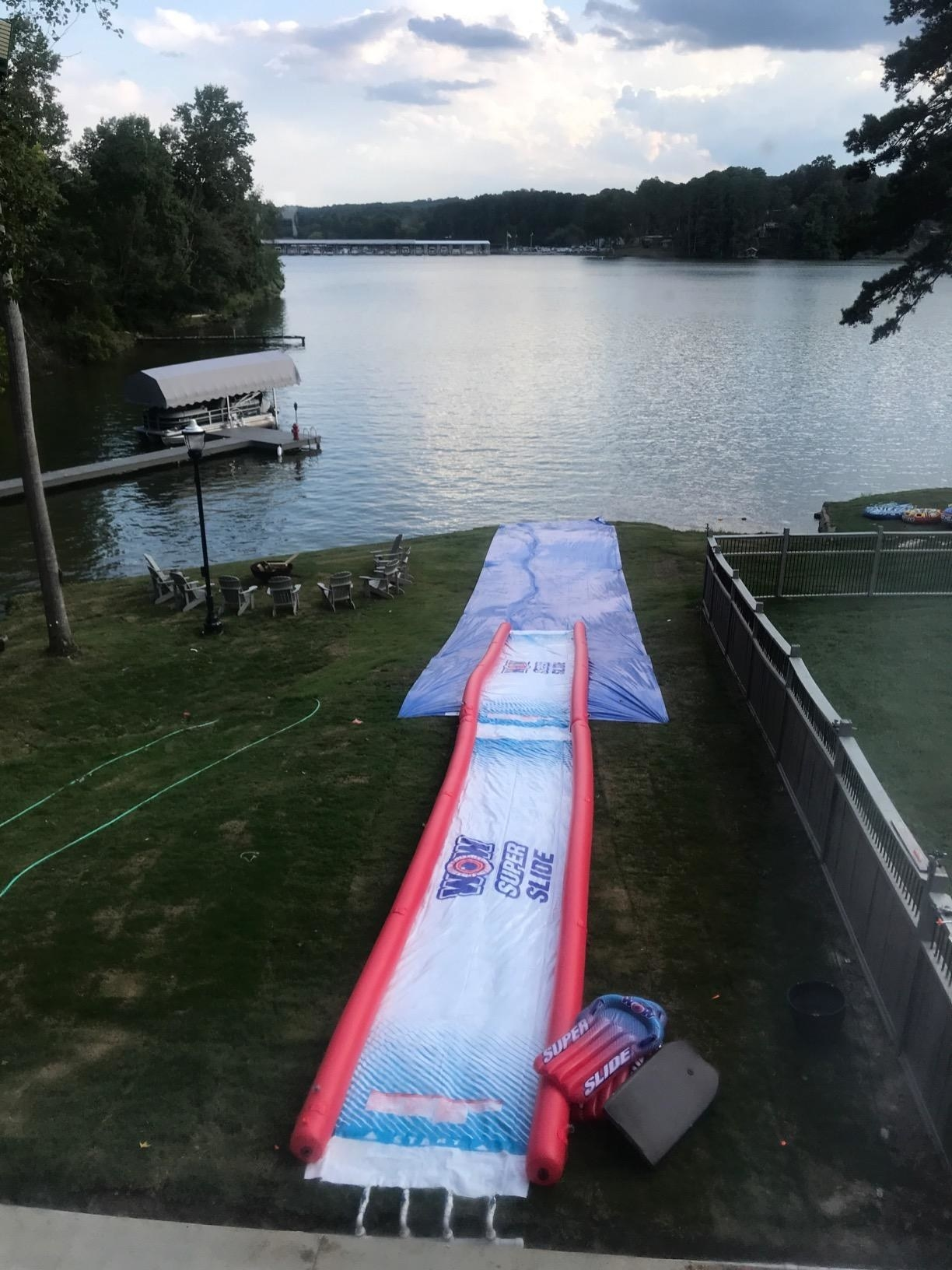 A super slide set up right in front of a lake.