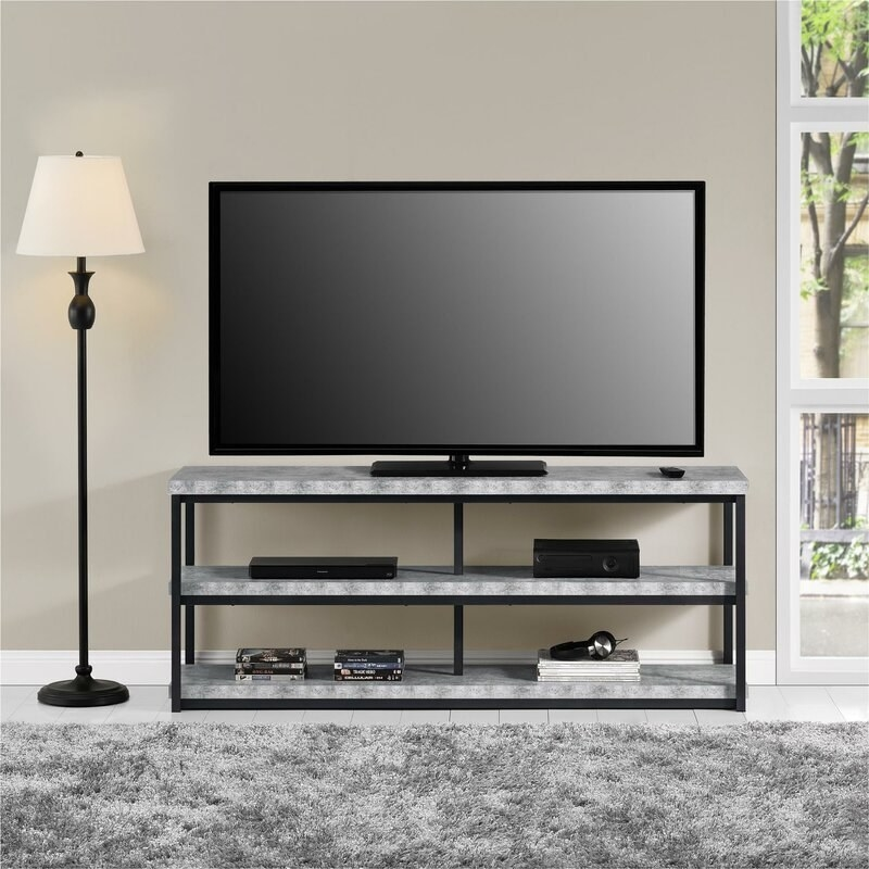Flat-screen TV sits on the three-tiered TV stand, made of a black metal frame and wooden shelves powdered to look like concrete