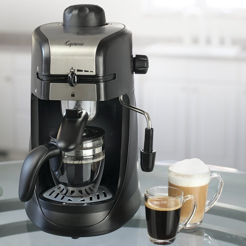 A black and stainless steel machine with a glass carafe set on the tray. A cup of espresso and a cappuccino are set next to it