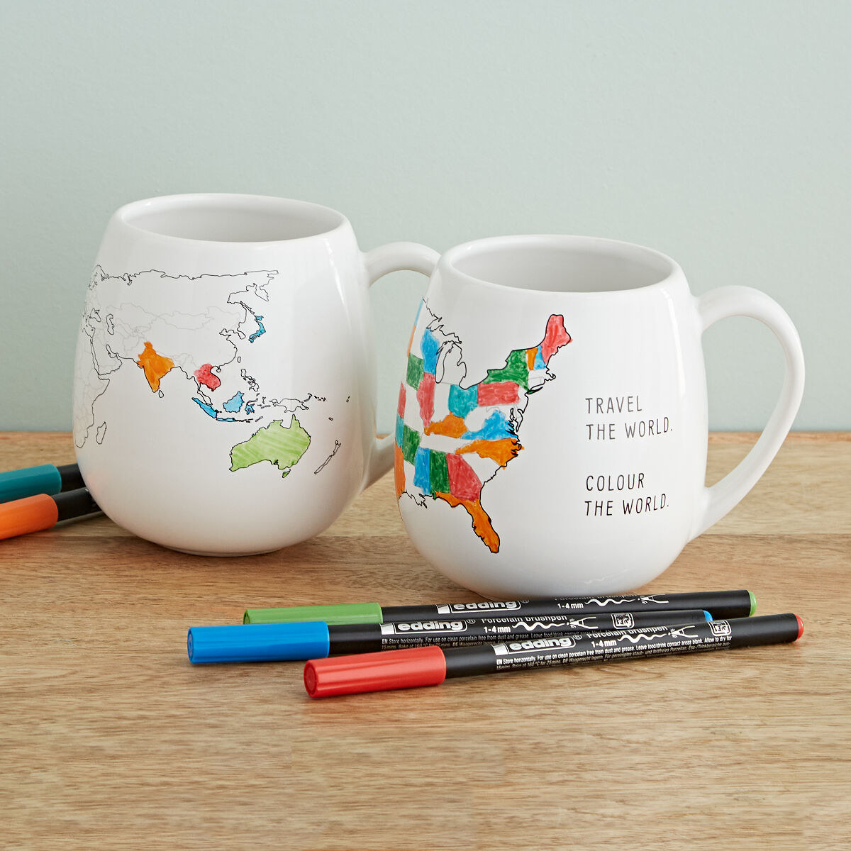 Three colored markers and two mugs with maps of the U.S and the world, partially colored in.