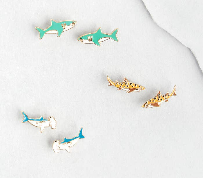 Three pairs of earrings shaped like great white sharks, hammerhead sharks, and leopard sharks