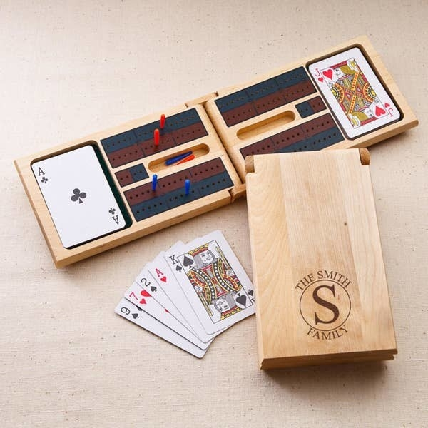 Open wooden cribbage board with two compartments for a deck of cards at each end and pegs in the holes with another cribbage board closed showing the personalization and a hand of cards next to it