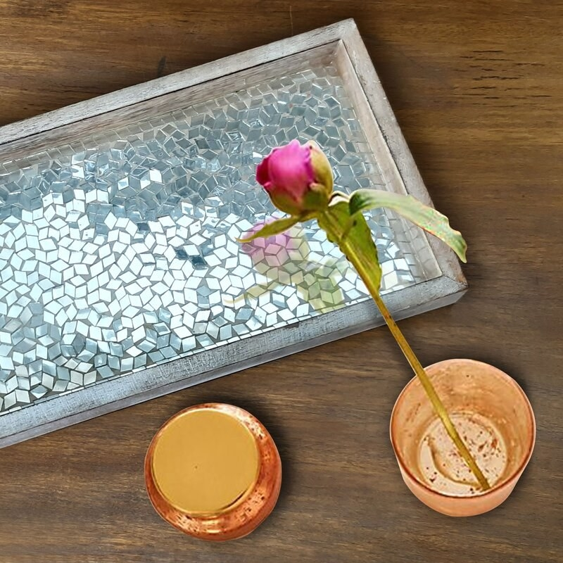 A wooden tray painted silver, with a metallic, mosaic inlay
