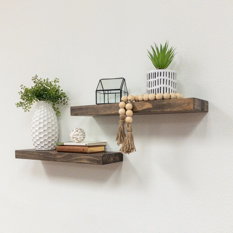 Two floating shelves stacked on a wall with home decor atop each