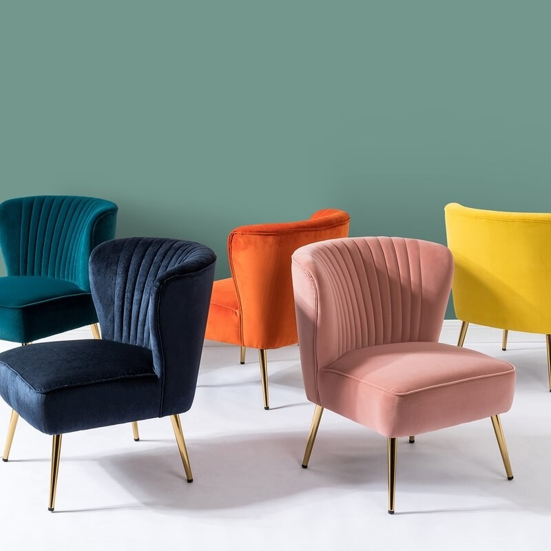 Multiple side chairs in different colors, each with a rounded, tufted back and tapered metal legs